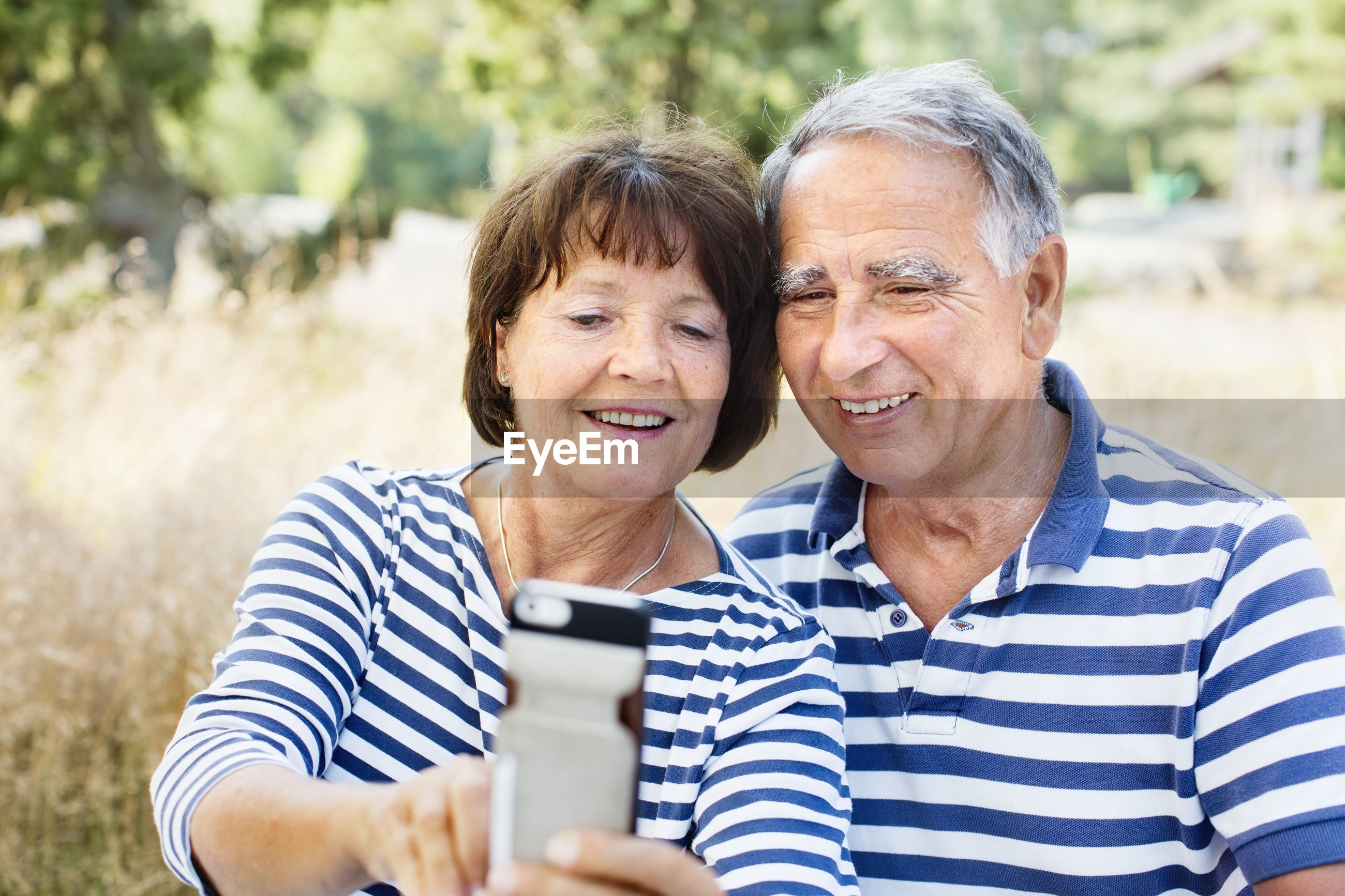 PORTRAIT OF MAN AND WOMAN USING PHONE OUTDOORS