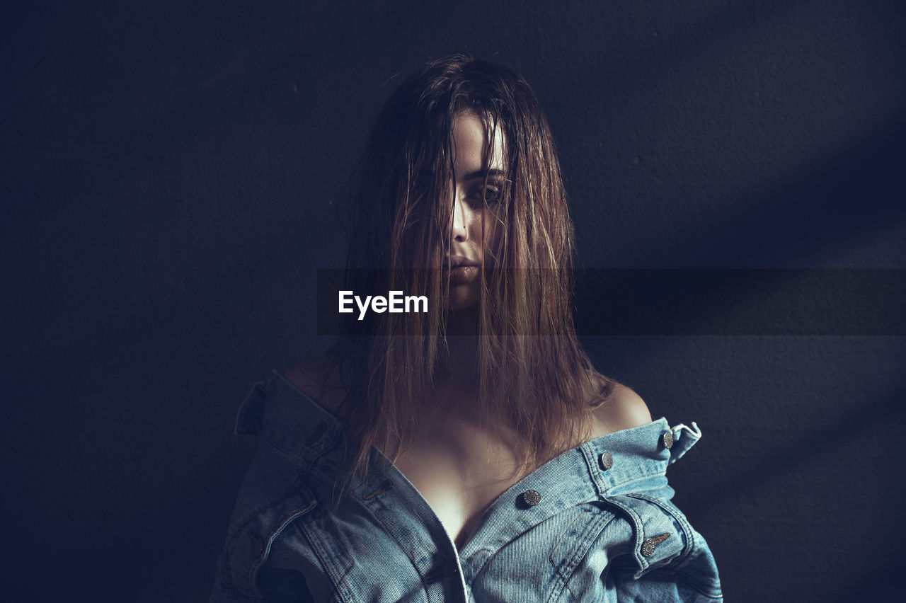 Portrait of sensuous woman wearing denim jacket standing against wall