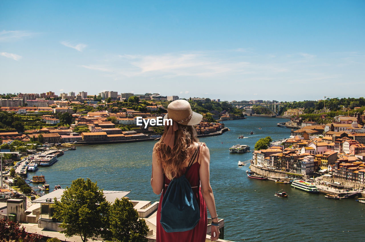 Rear View Of Young Woman With Backpack Looking At River Against Sky In City