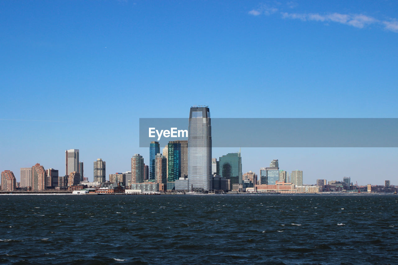 architecture, built structure, building exterior, sky, city, urban skyline, waterfront, office building exterior, building, water, landscape, skyscraper, modern, clear sky, tall - high, cityscape, blue, office, nature, no people, outdoors, financial district