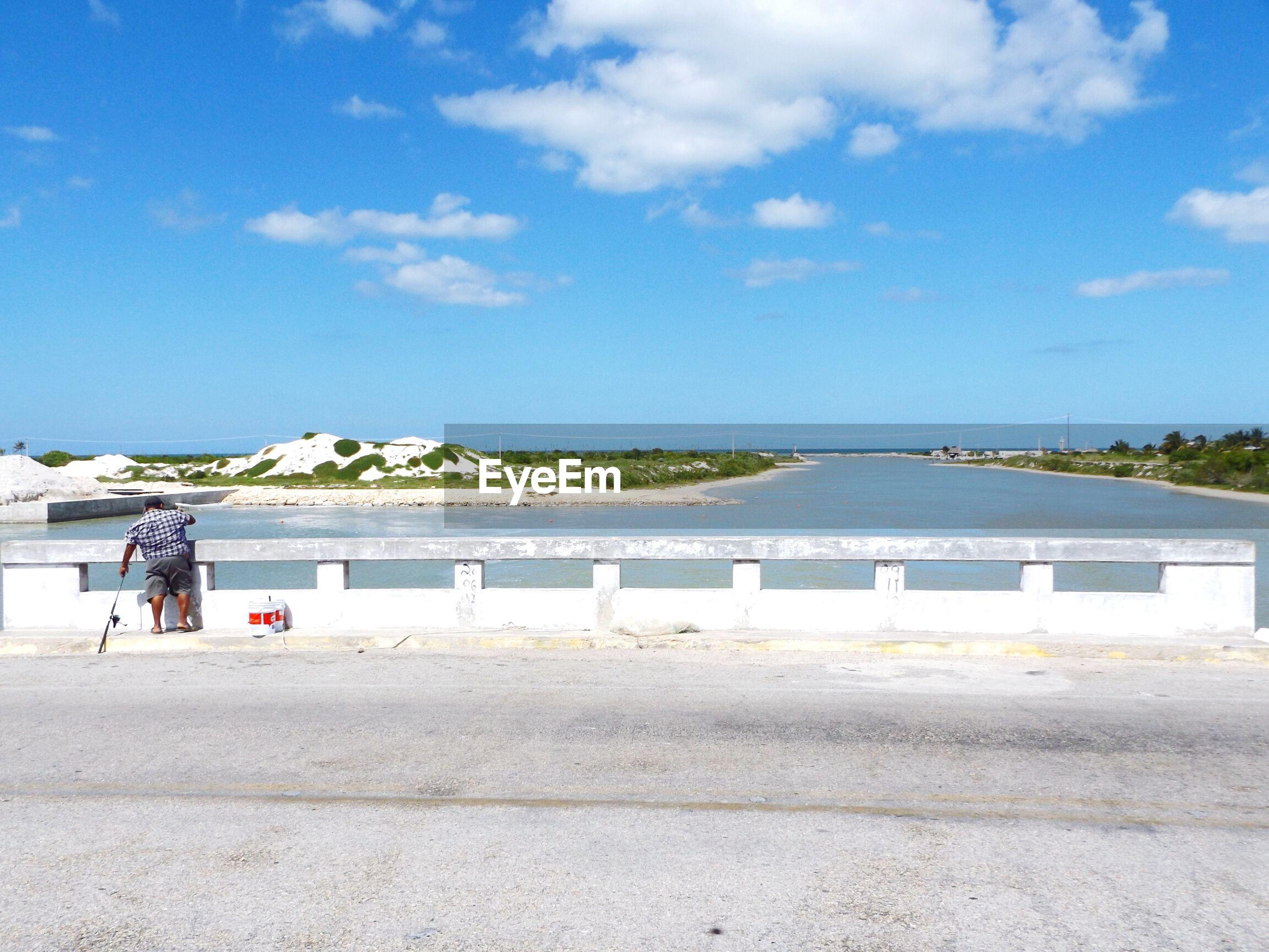 Man standing at railing on bridge over sea against sky