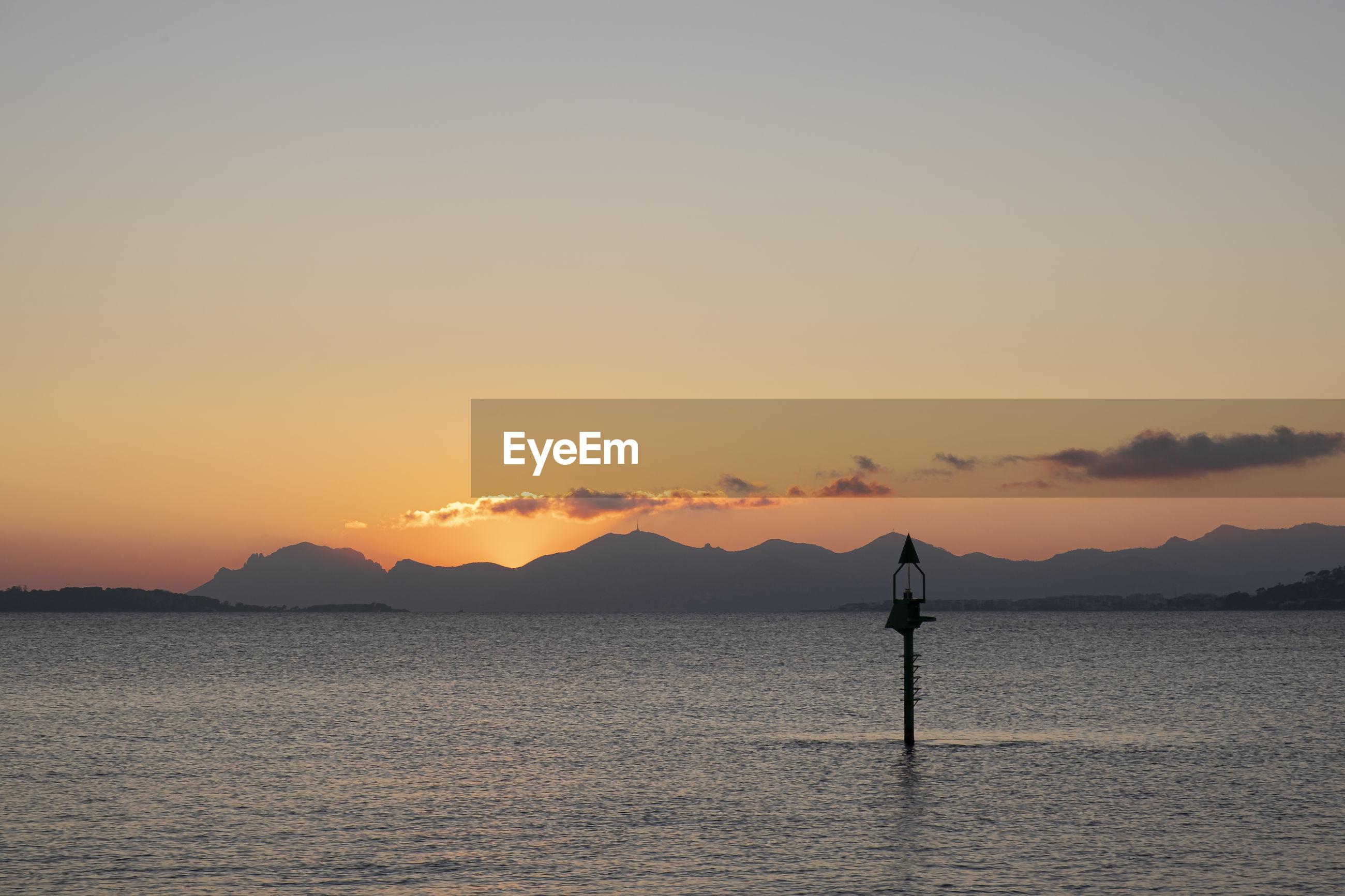 SILHOUETTE PERSON STANDING IN SEA AGAINST ORANGE SKY