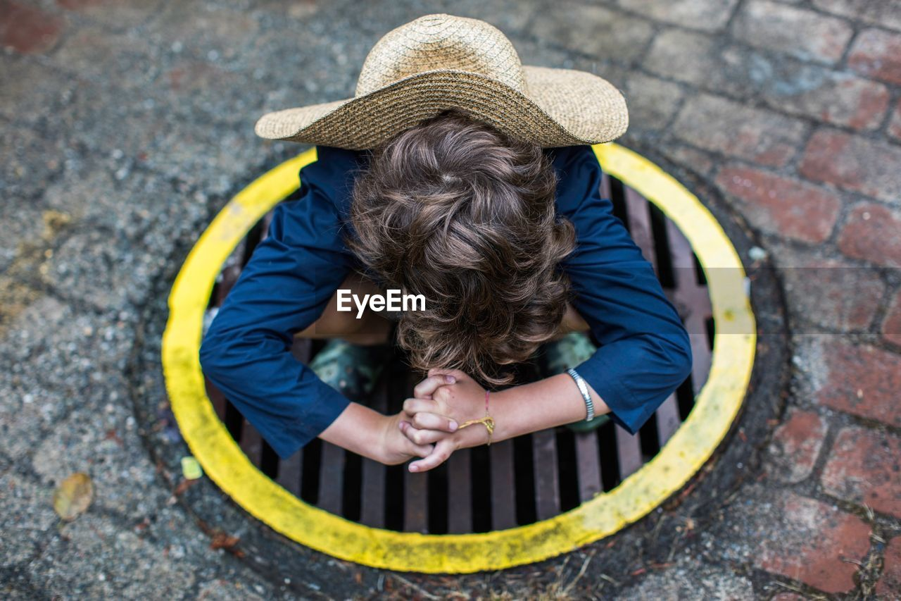 High angle view of boy wearing hat while crouching on manhole