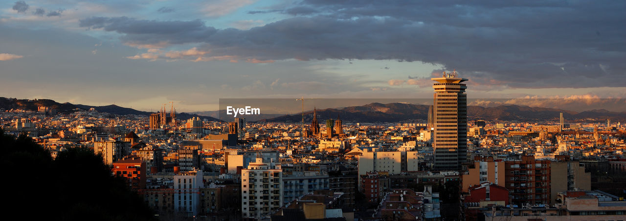 Panoramic Shot Of Cityscape Against Cloudy Sky At Sunset