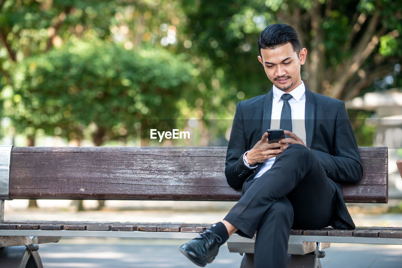 business person, suit, businessman, one person, well-dressed, business, technology, wireless technology, men, day, bench, corporate business, mobile phone, sitting, males, focus on foreground, front view, communication, connection, formalwear, outdoors