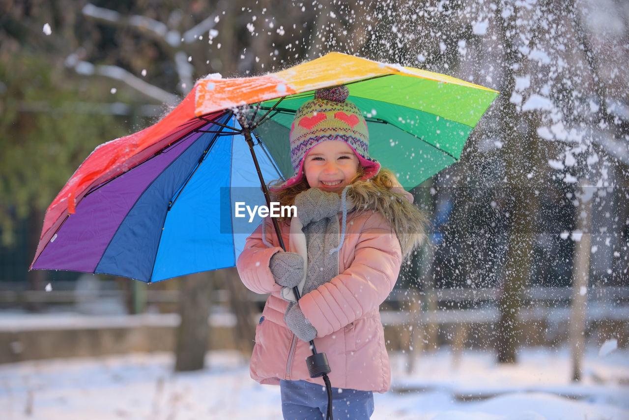 Portrait Of Happy Girl Holding Umbrella During Winter