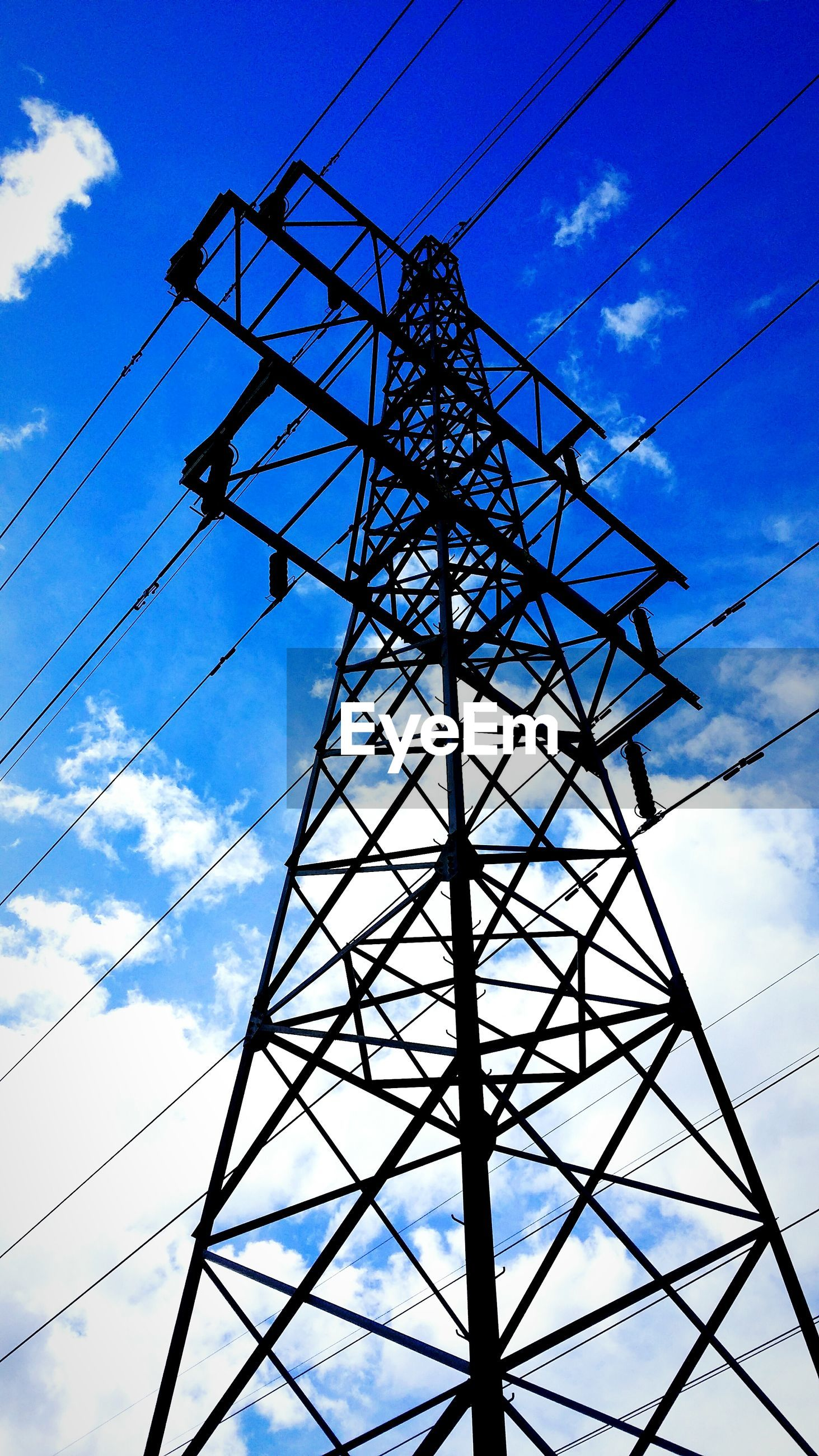 Low angle view of electricity pylon against cloudy blue sky