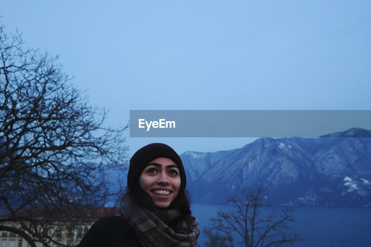 Smiling Young Woman Looking Away Against Mountains And Sky