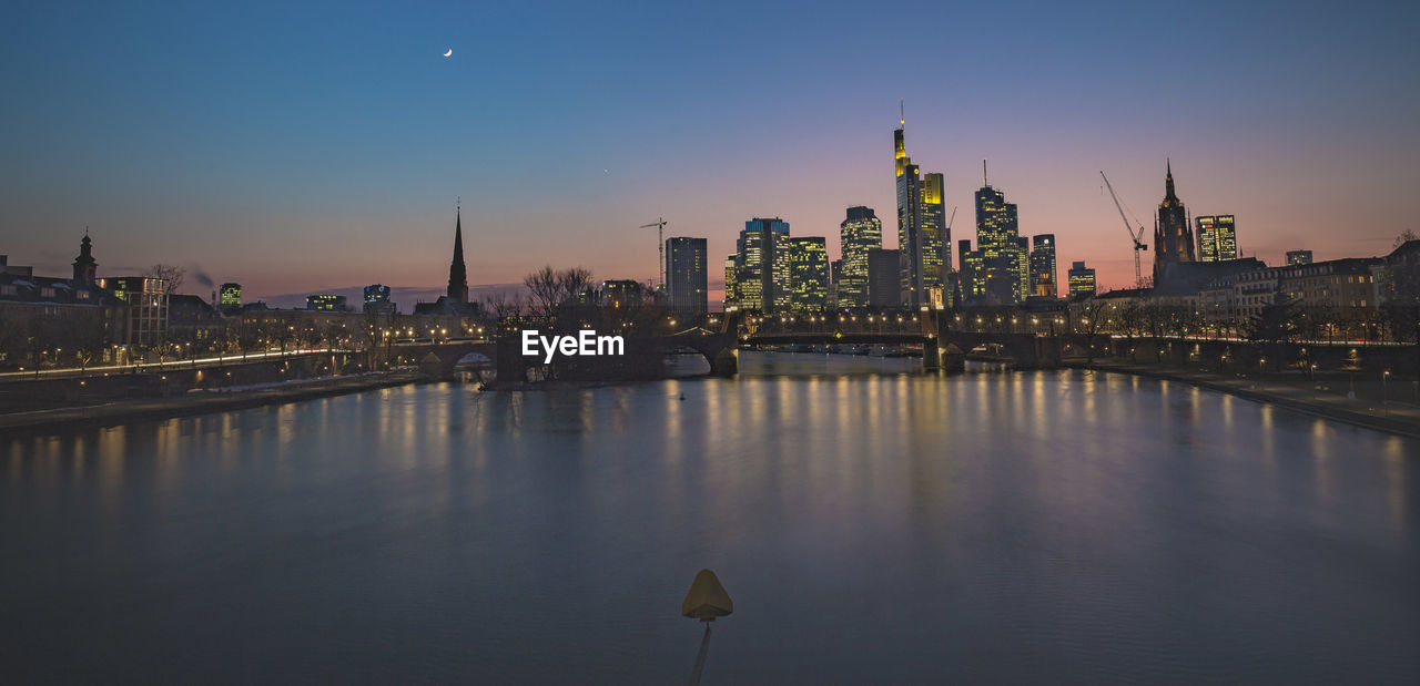 View of river against illuminated buildings during sunset
