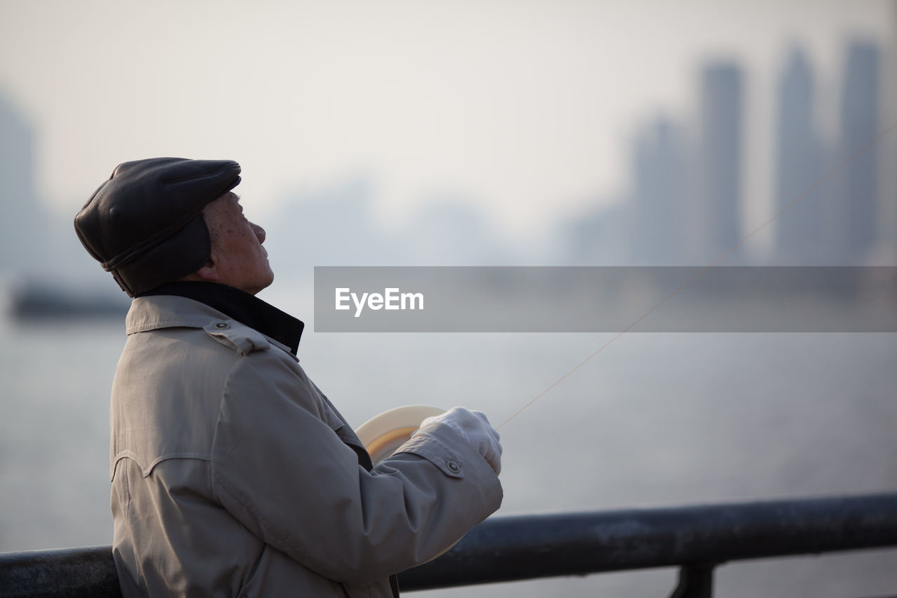 real people, one person, focus on foreground, outdoors, holding, day, men, sea, sky, nature, city, close-up, people
