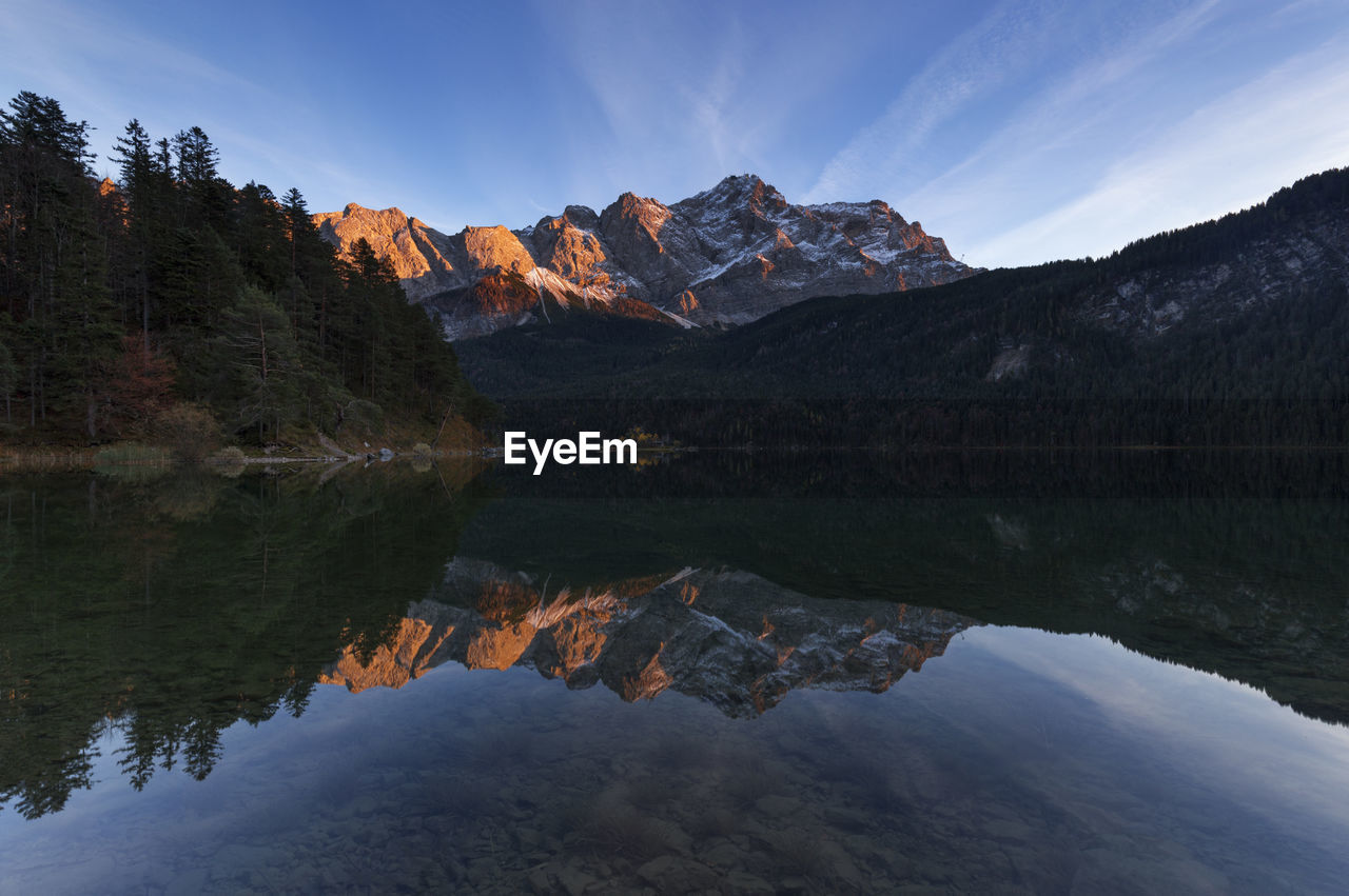 Scenic View Of Lake With Mountain Reflection Against Blue Sky