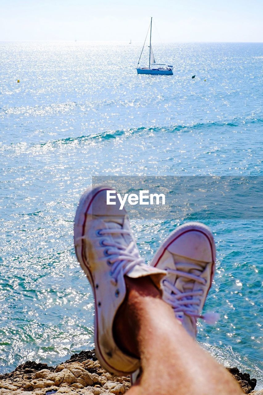 water, sea, low section, human leg, human body part, shoe, personal perspective, one person, real people, lifestyles, body part, day, leisure activity, nature, horizon, transportation, nautical vessel, horizon over water, relaxation, outdoors, human foot