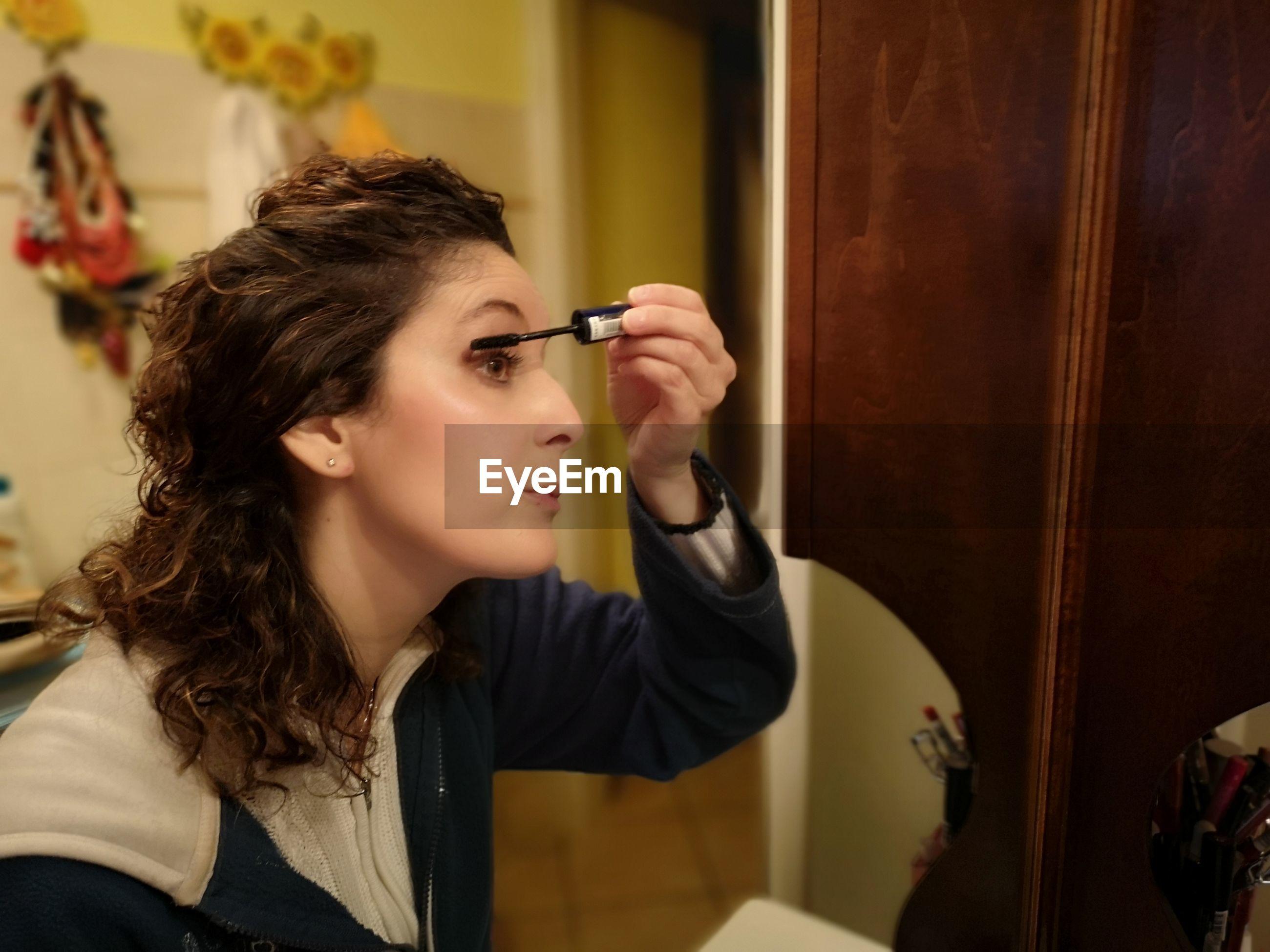 Mature woman applying mascara at home