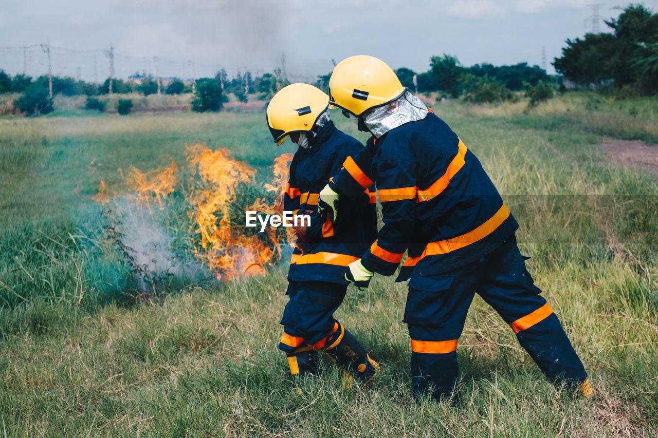 Firefighters By Fire On Field