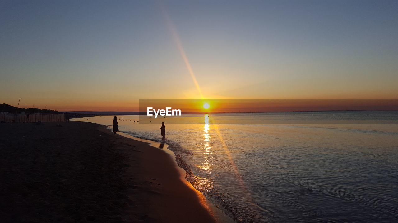 sky, water, sunset, sea, beauty in nature, scenics - nature, beach, land, tranquility, sunlight, sun, tranquil scene, horizon, horizon over water, nature, reflection, idyllic, non-urban scene, sunbeam, lens flare, outdoors