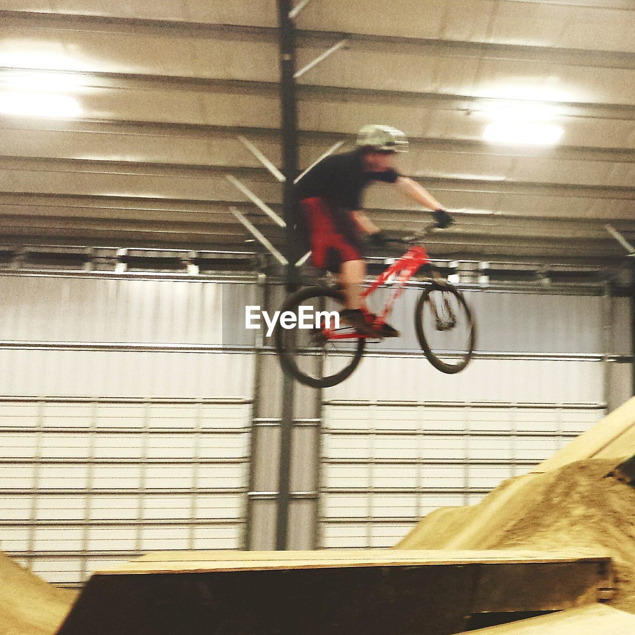 blurred motion, motion, bicycle, full length, speed, one person, men, illuminated, real people, indoors, transportation, mid-air, risk, stunt, low angle view, skill, headwear, day, sportsman, young adult, people