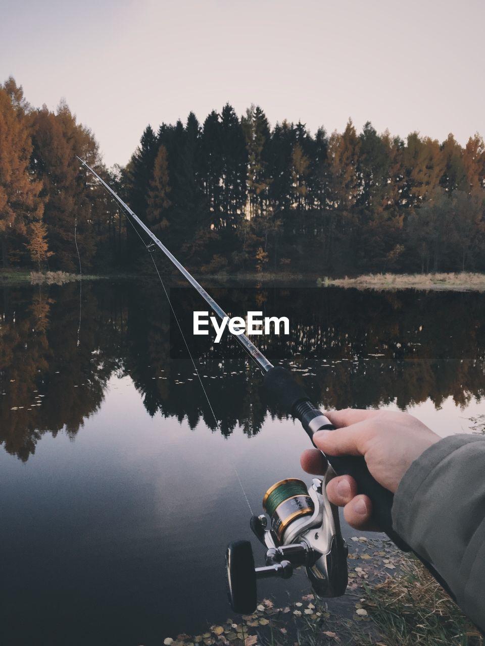 Cropped image of hand holding fishing rod at lakeshore