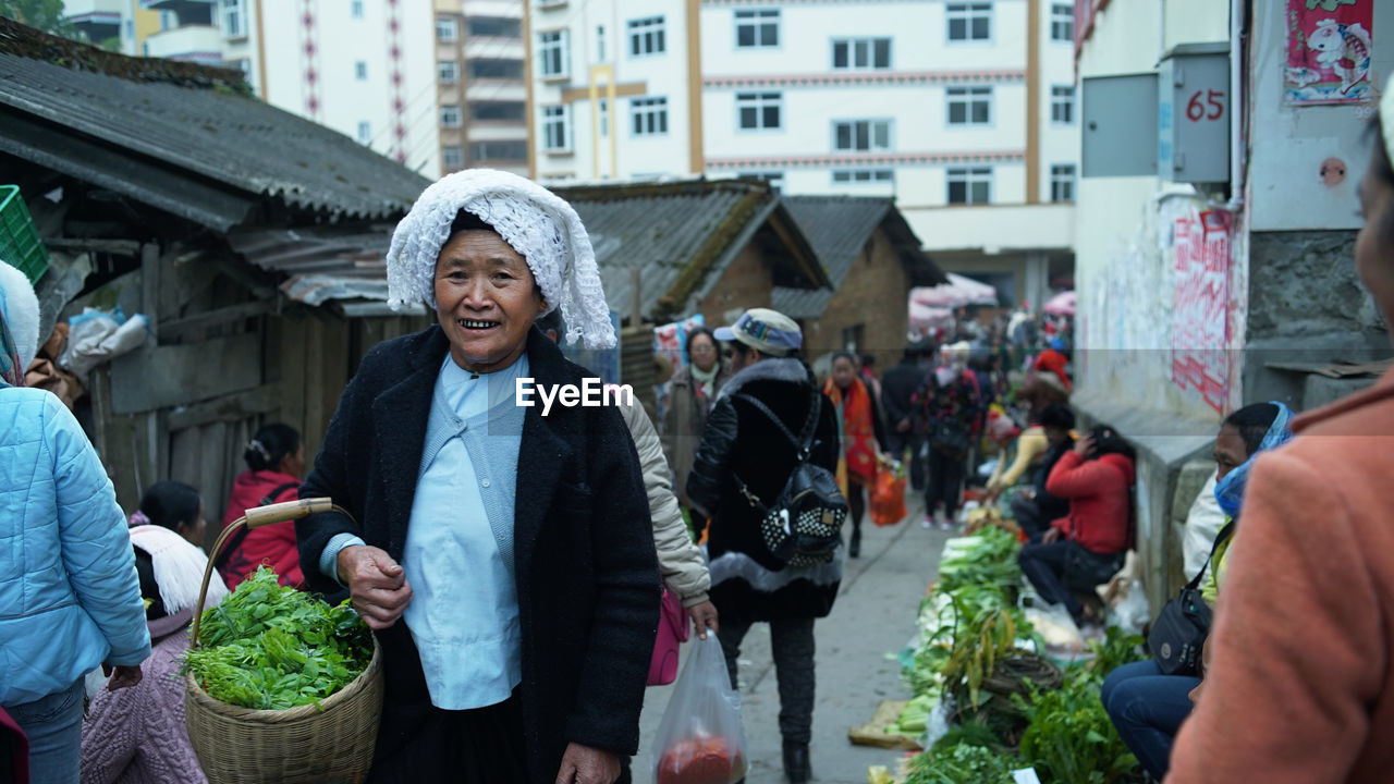 real people, vegetable, incidental people, day, outdoors, market, lifestyles, building exterior, retail, women, leisure activity, freshness, built structure, architecture, men, food, healthy eating, smiling, warm clothing, one person, people