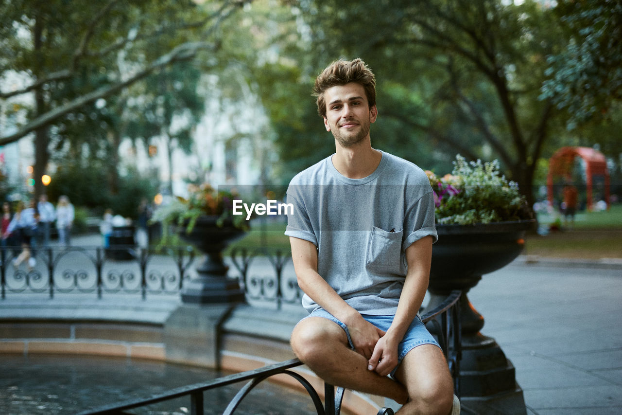 Portrait Of Young Man Sitting By Fountain At Park