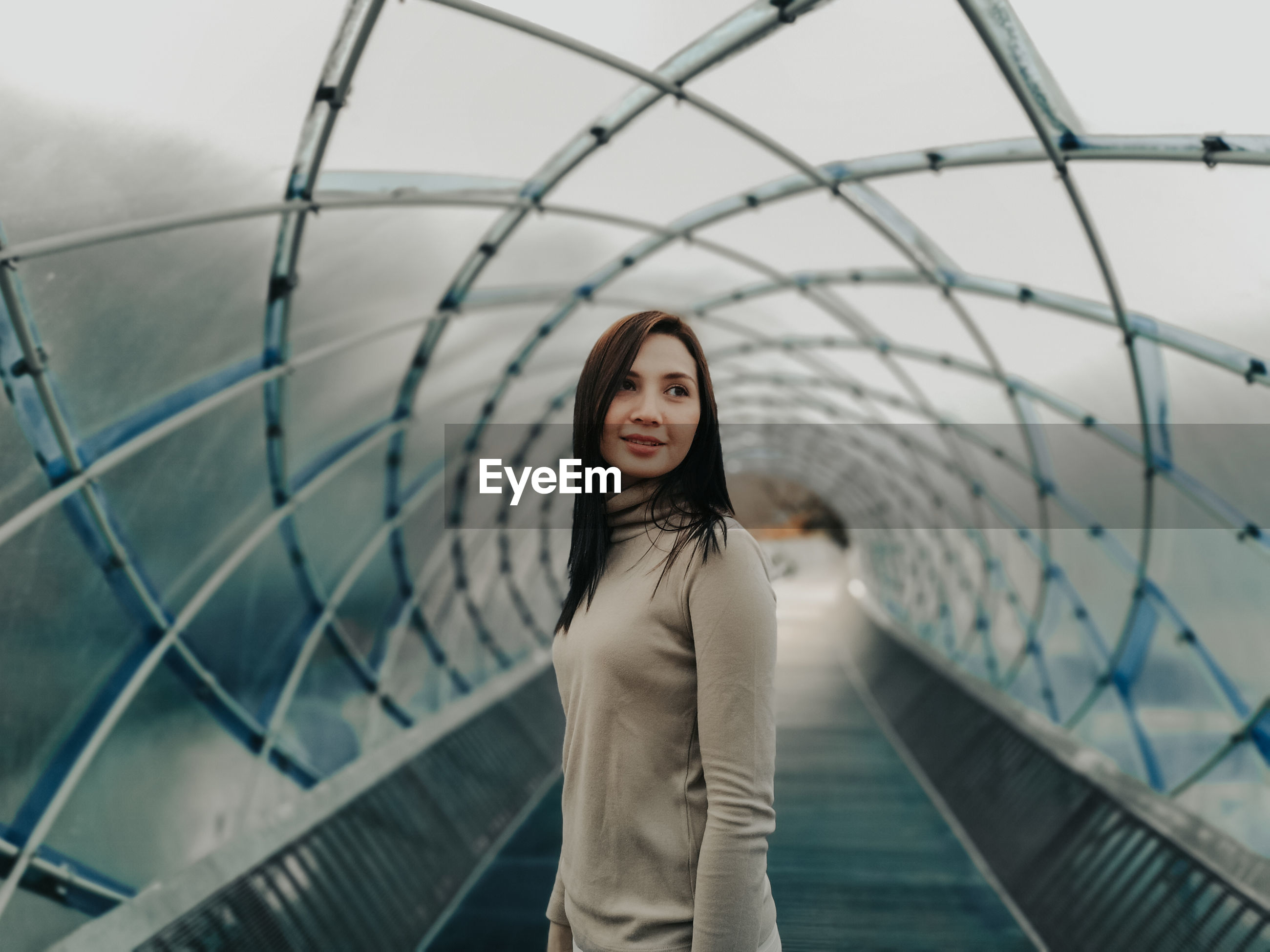 Woman standing under covered bridge