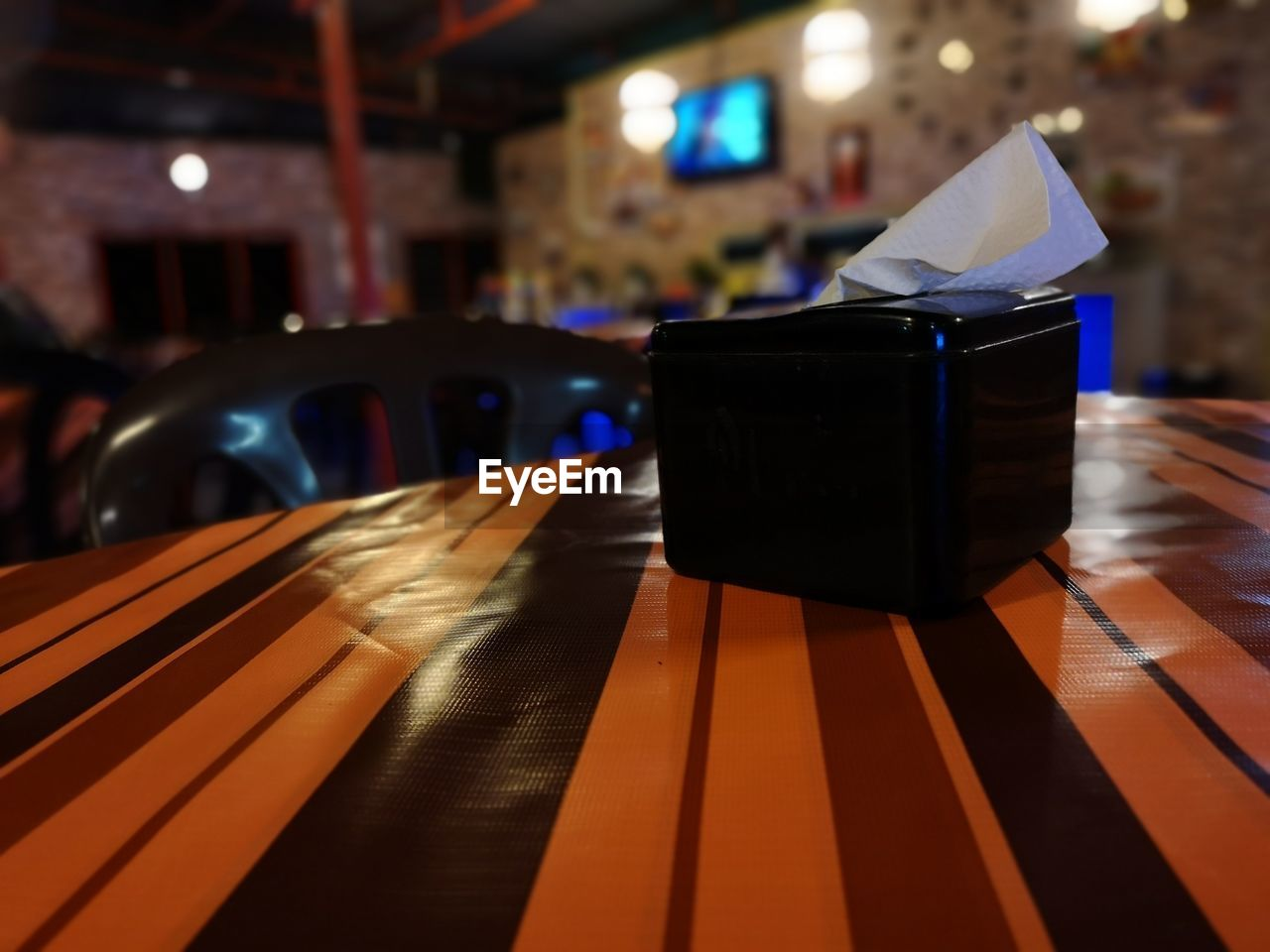 indoors, focus on foreground, illuminated, table, close-up, no people, wood - material, still life, paper, seat, night, restaurant, flooring, chair, luxury, lighting equipment, wealth