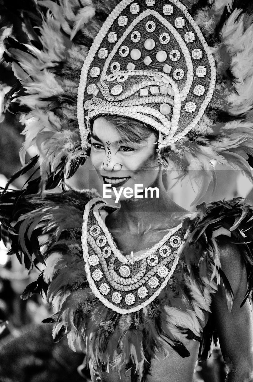 costume, celebration, real people, venetian mask, mask - disguise, carnival, cultures, carnival - celebration event, one person, dancer, arts culture and entertainment, feather, lifestyles, traditional clothing, traditional festival, leisure activity, headdress, performance, young adult, young women, outdoors, day, smiling, close-up, people