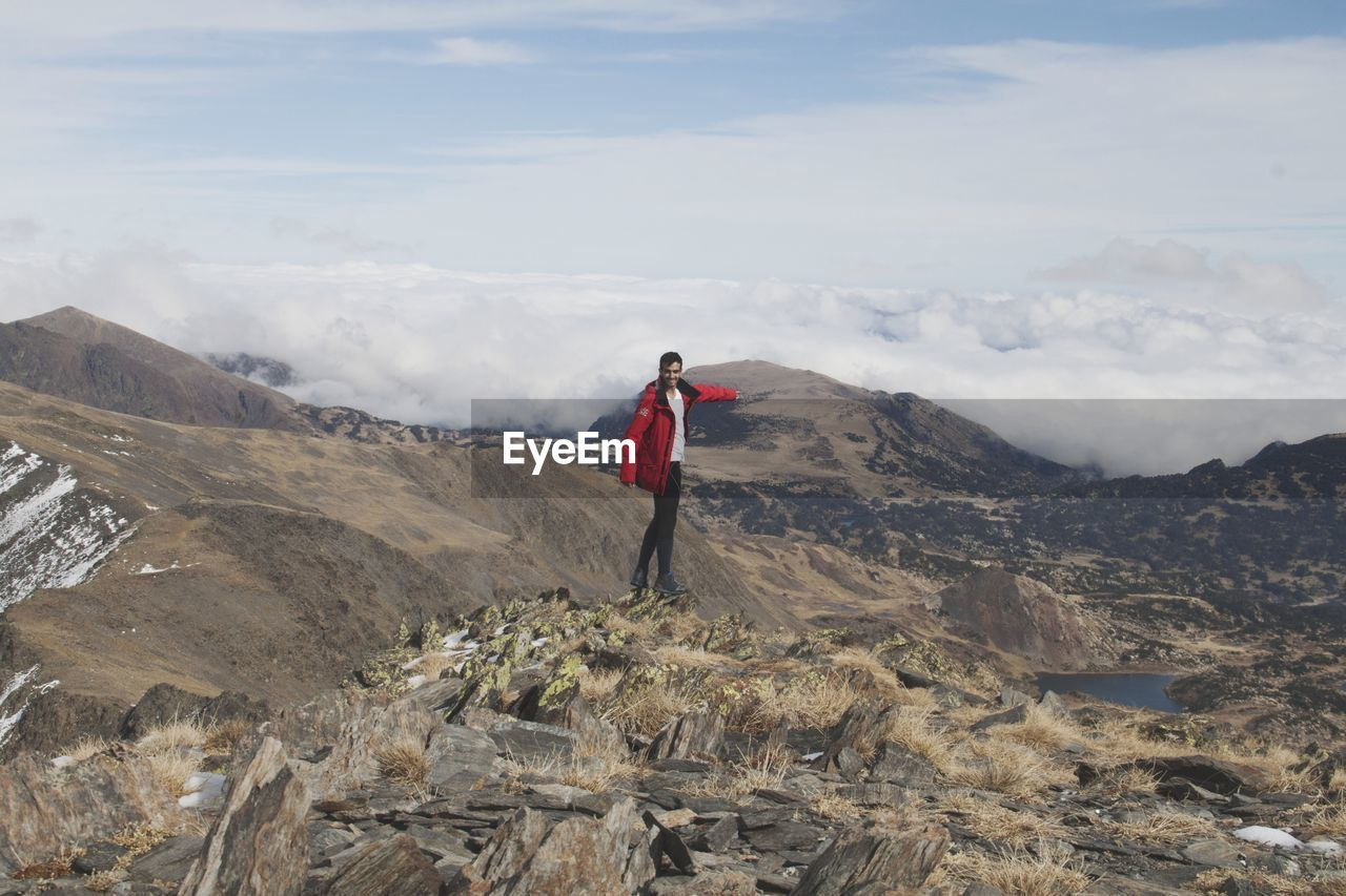 Young man with red jacket standing on mountain against sky.