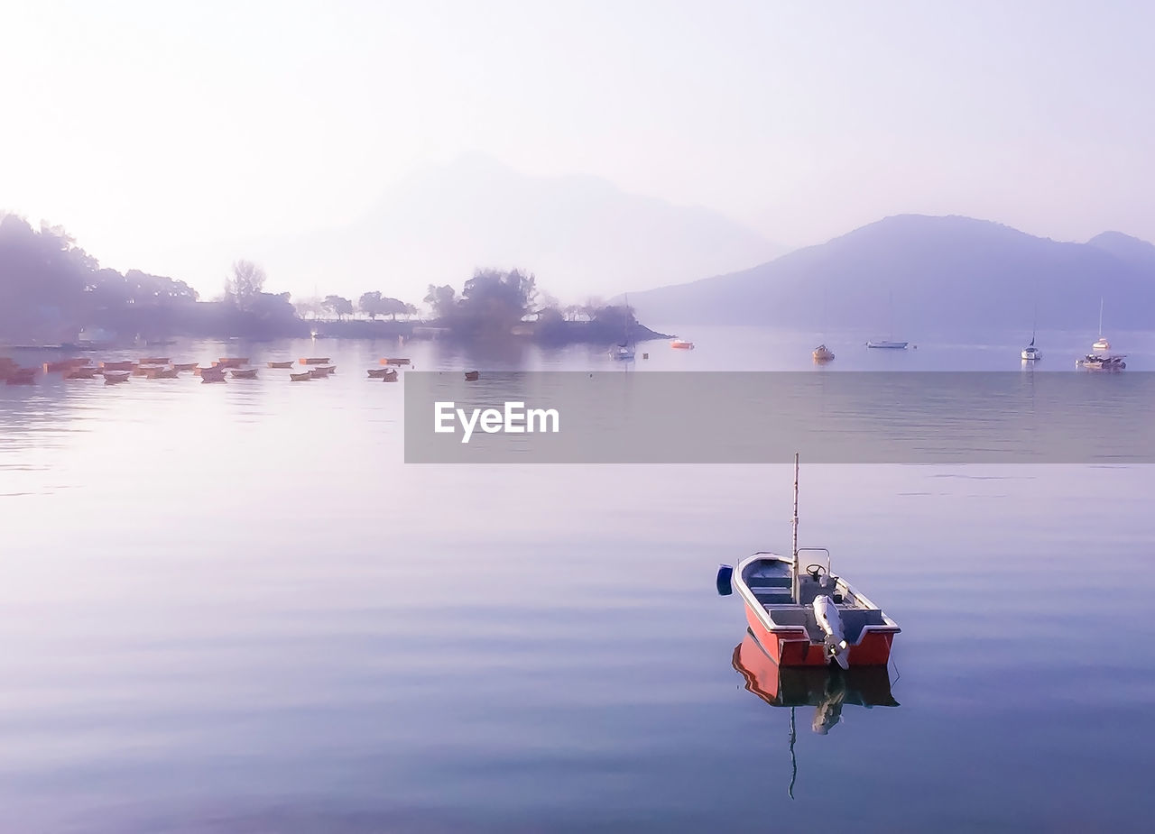 water, nautical vessel, transportation, sky, beauty in nature, mode of transportation, scenics - nature, waterfront, reflection, tranquility, tranquil scene, lake, nature, mountain, no people, non-urban scene, idyllic, fog, moored, outdoors