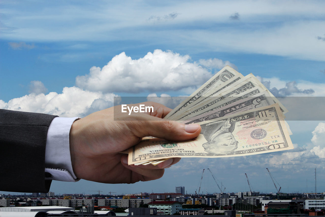 human hand, hand, finance, human body part, business, currency, sky, cloud - sky, paper currency, people, wealth, built structure, architecture, day, men, holding, nature, corporate business, opportunity, economy, finger