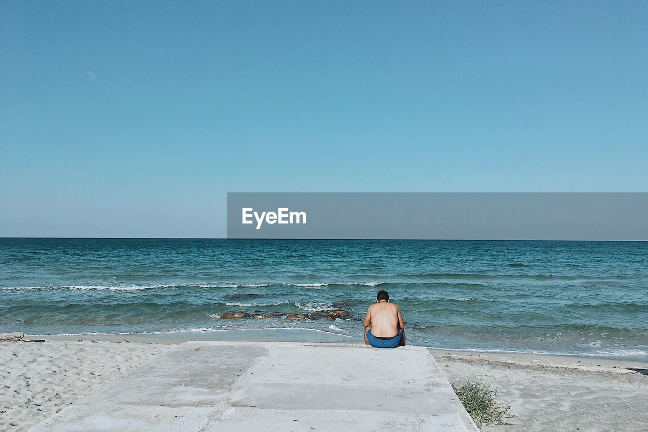 sea, water, sky, beach, horizon, land, horizon over water, scenics - nature, beauty in nature, one person, clear sky, leisure activity, real people, rear view, copy space, lifestyles, holiday, nature, vacations, outdoors