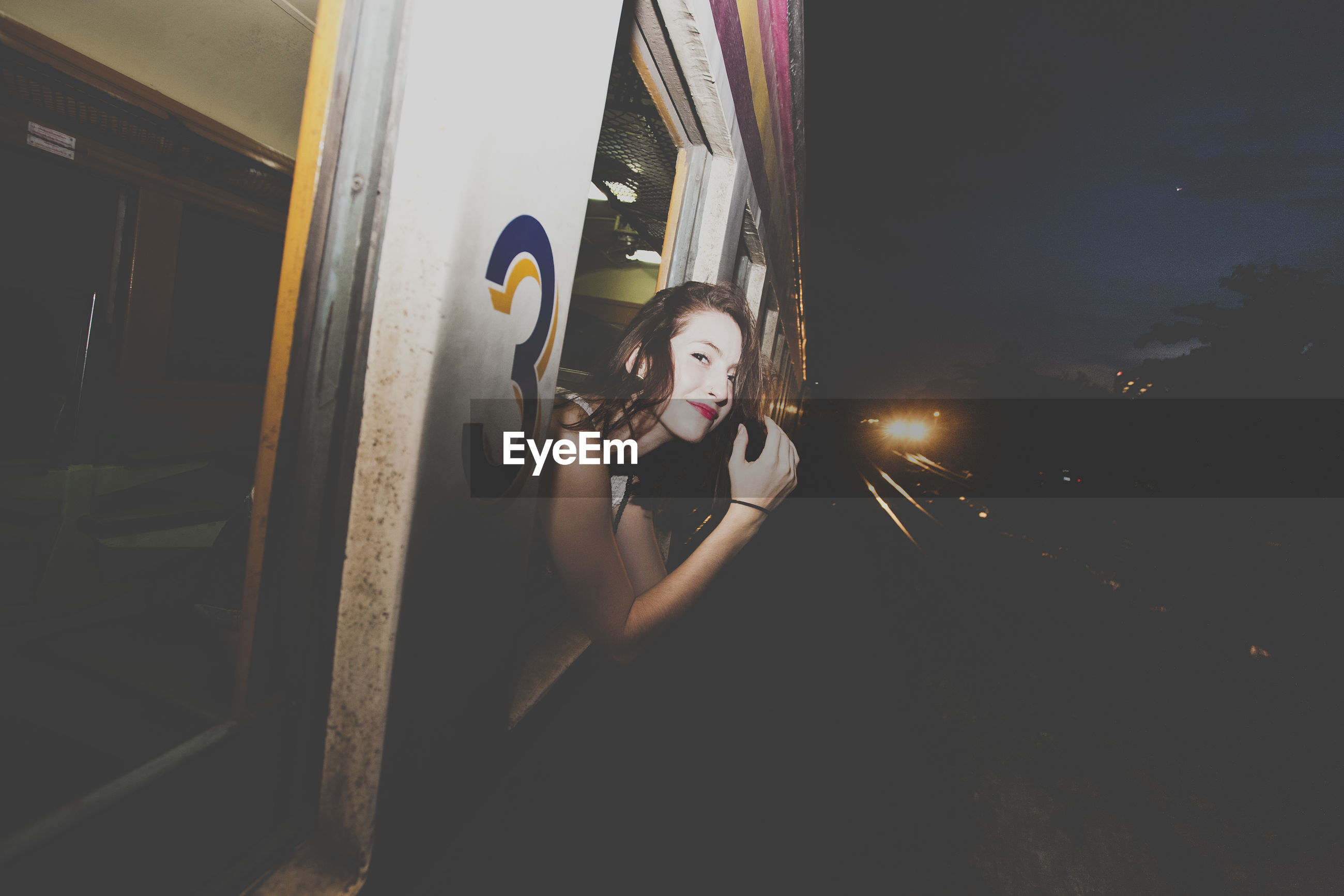 Portrait of young woman in train window