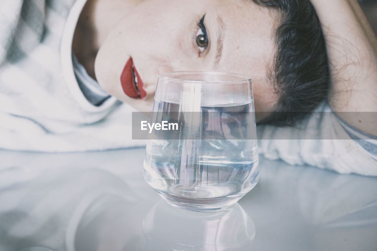 Close-up of woman holding glass of water