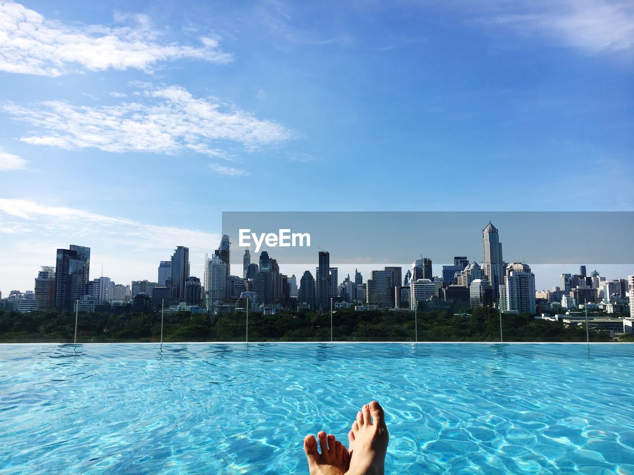 Low Angle View Of Person Floating On Swimming Pool Against City