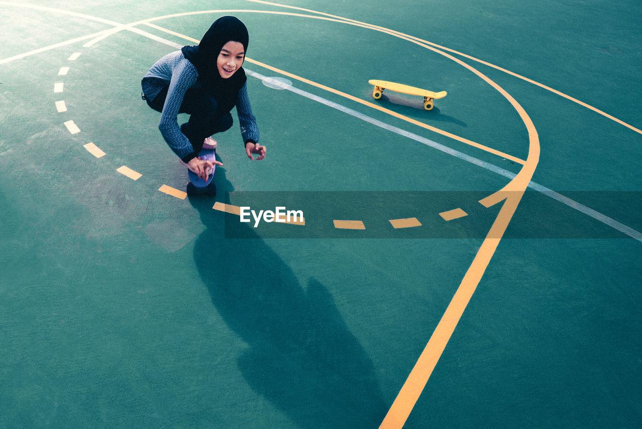 High angle view of teenage girl skateboarding at basketball court