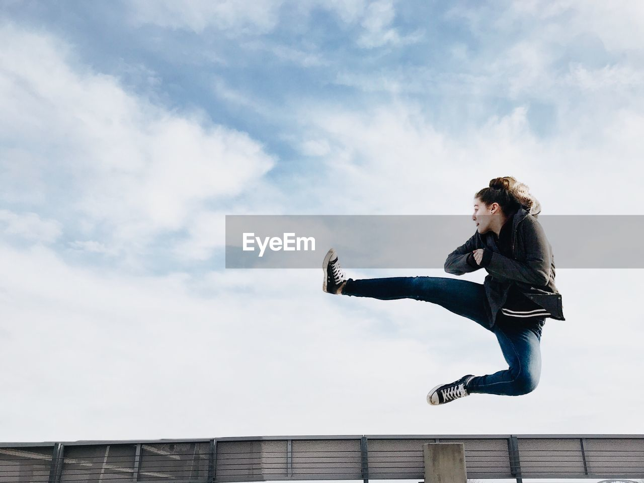 Full Length Of Woman Jumping Against Cloudy Sky