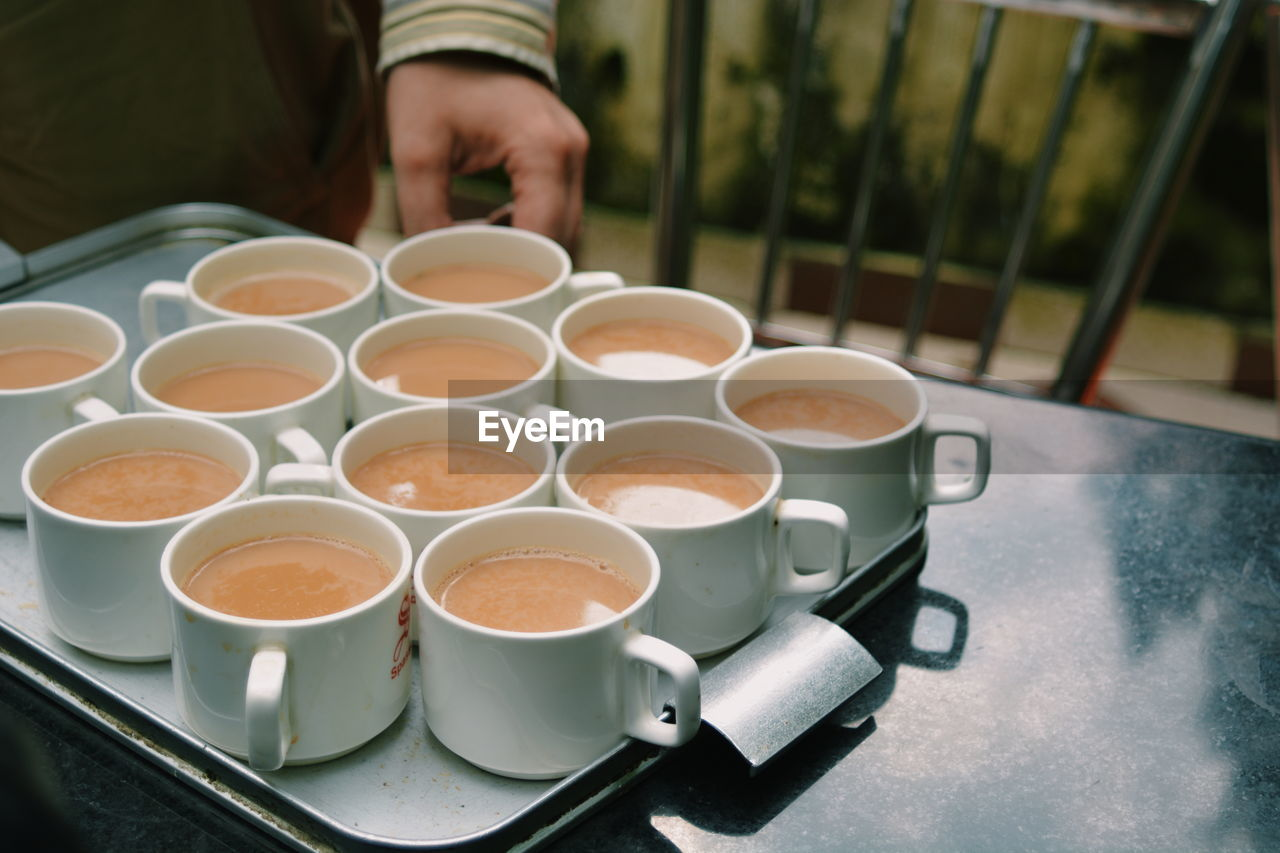 Midsection Of Man Hand By Tea Cups In Tray On Table