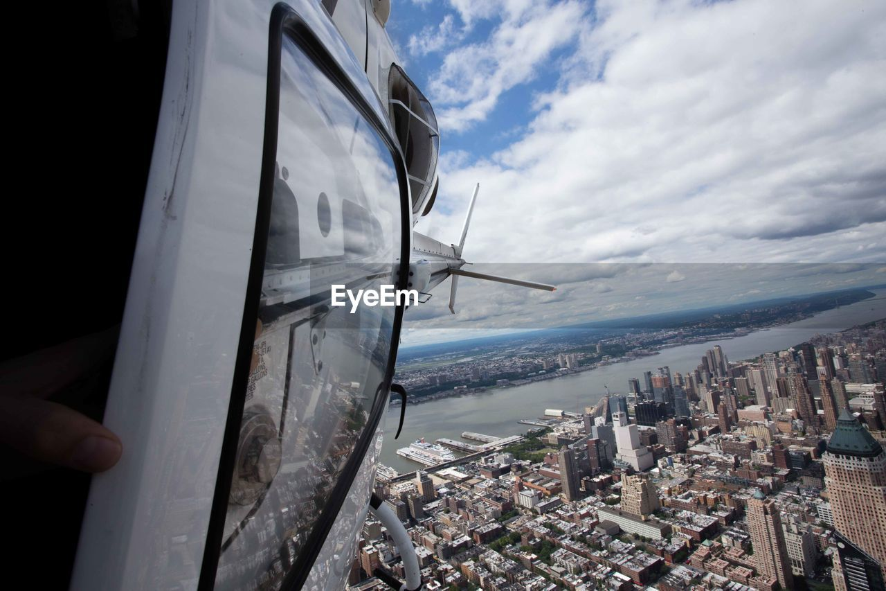 Close-Up Of Helicopter Flying Over Cityscape Against Sky