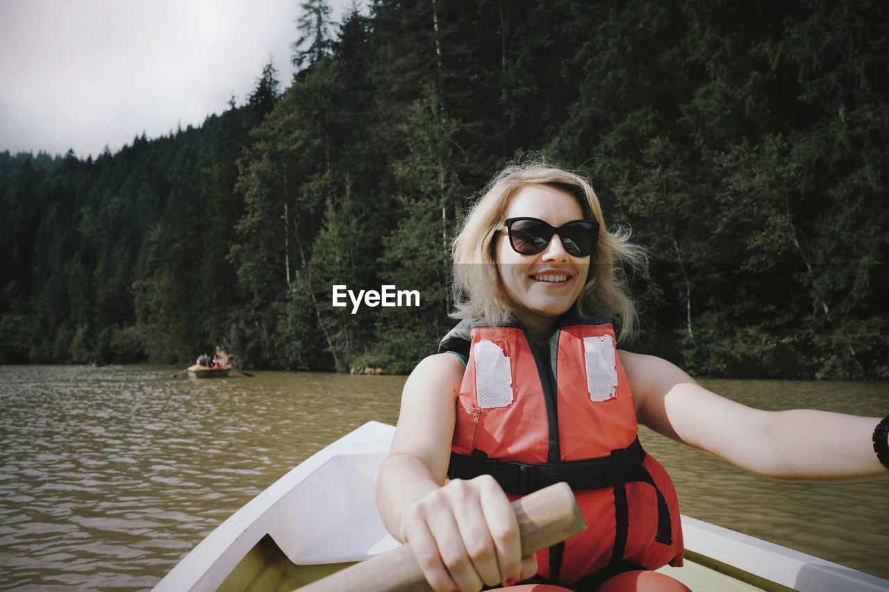 Smiling Woman Wearing Sunglasses And Life Jacket Sitting On Boat In Lake