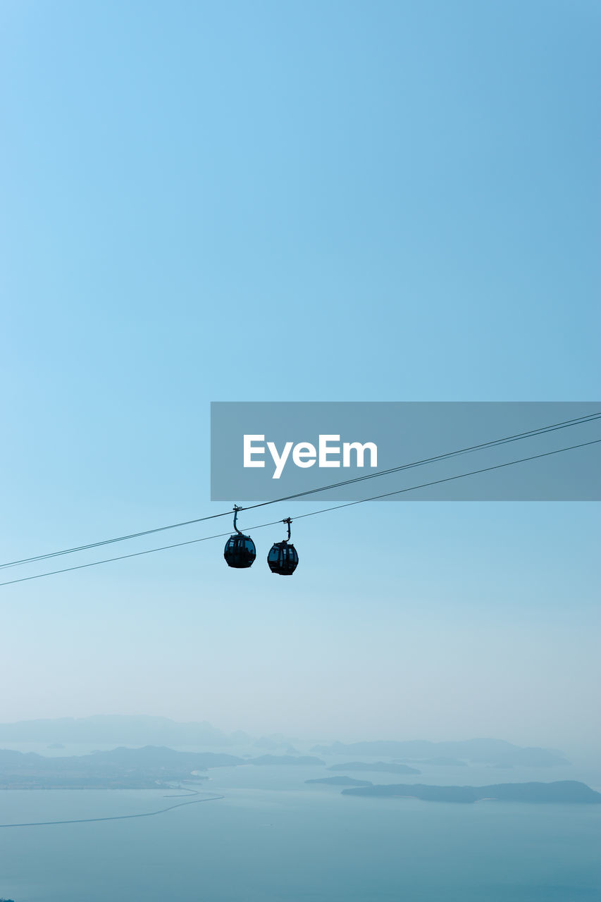 sky, cable, cable car, overhead cable car, copy space, scenics - nature, no people, nature, blue, electricity, low angle view, clear sky, beauty in nature, hanging, day, tranquility, connection, tranquil scene, outdoors, power line