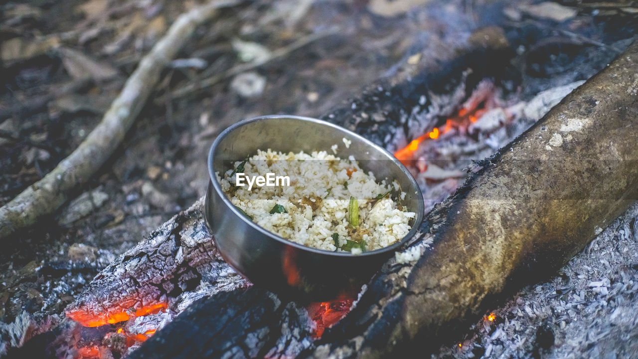 High Angle View Of Food In Bowl Cooking On Bonfire