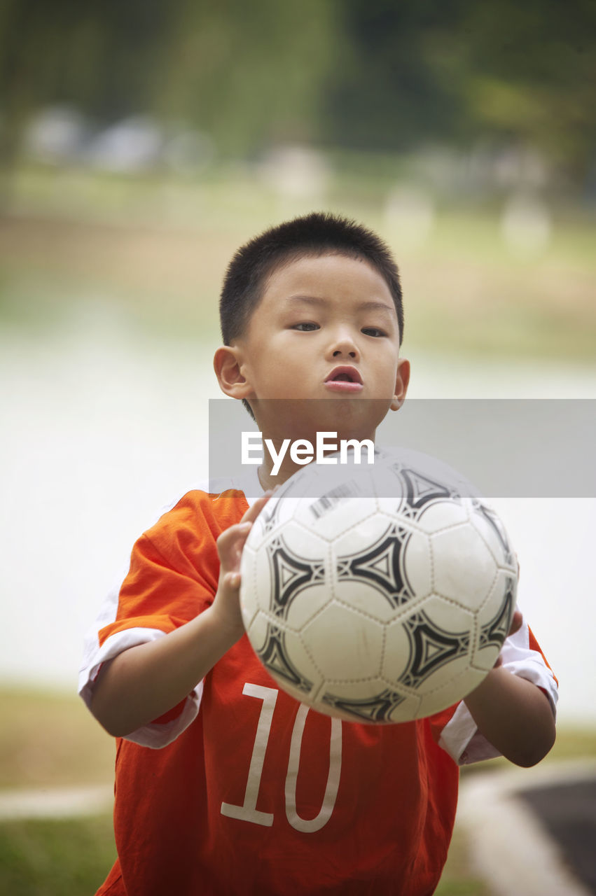 Boy Playing Soccer On Field At Park