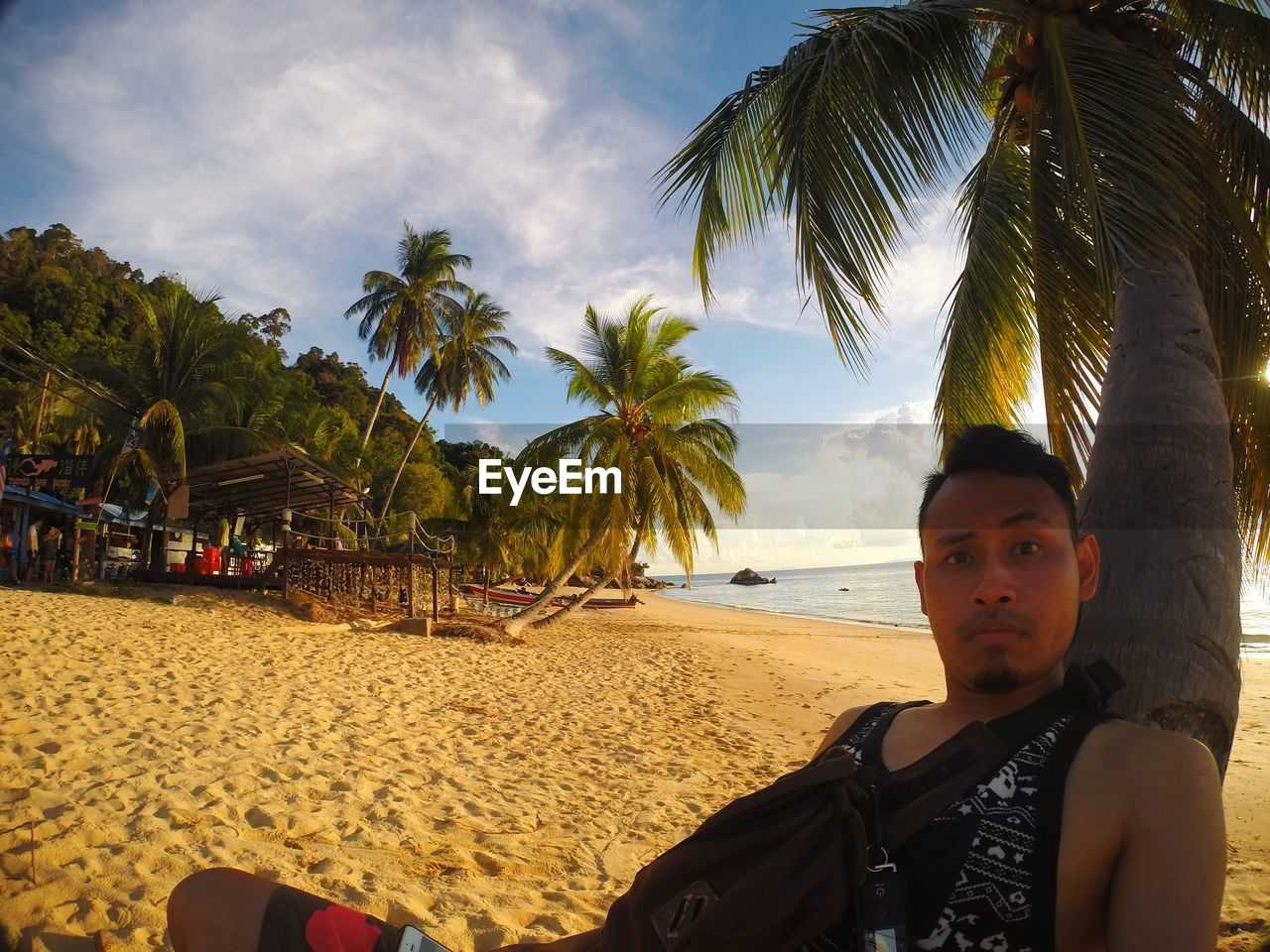 tropical climate, palm tree, beach, tree, land, sky, real people, sand, one person, leisure activity, plant, lifestyles, looking at camera, nature, portrait, beauty in nature, young adult, sea, sitting, young men, outdoors, coconut palm tree