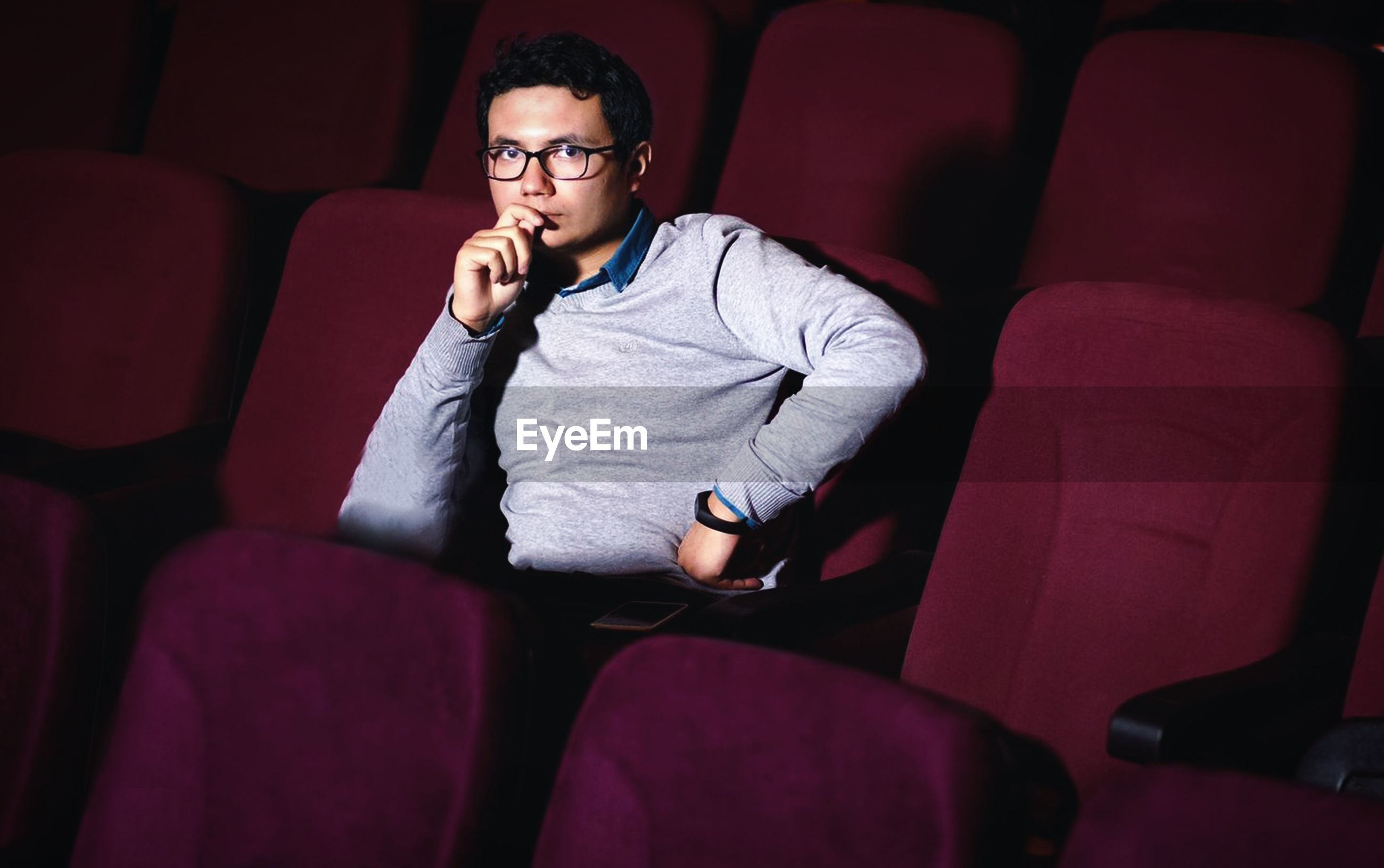 Young man sitting on seat in theater