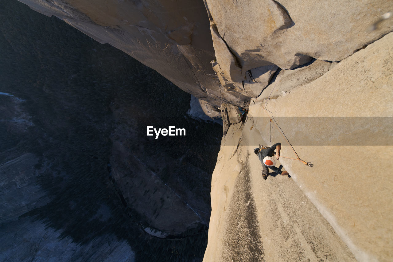 HIGH ANGLE VIEW OF MEN WALKING ON ROCK