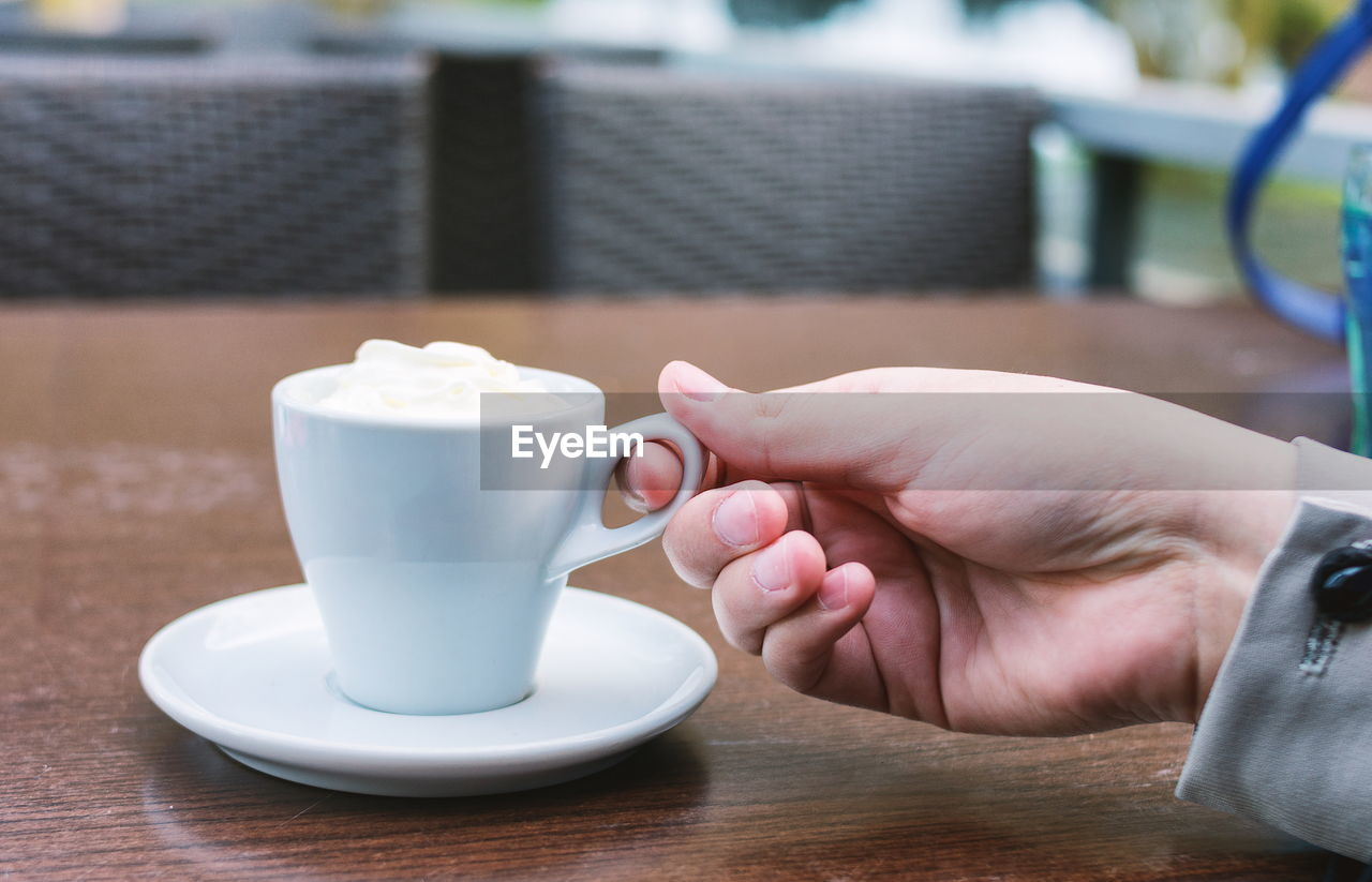 CLOSE-UP OF HAND HOLDING COFFEE CUP ON TABLE AT CAFE
