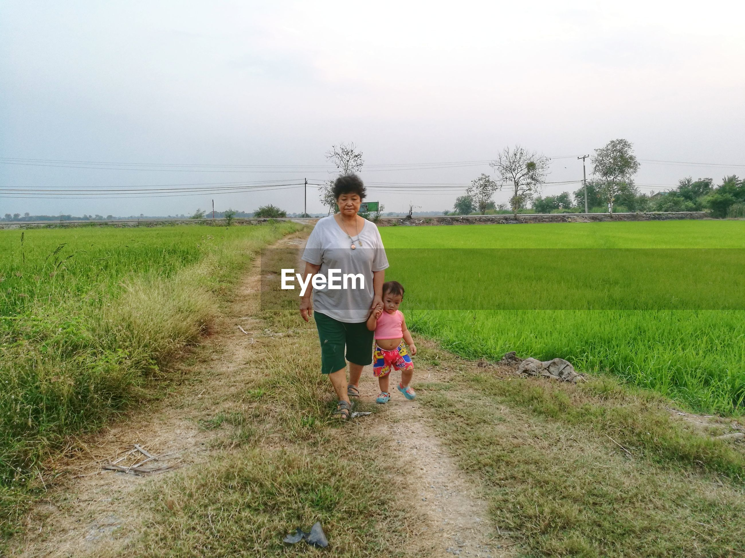 Woman walking with granddaughter on field against sky