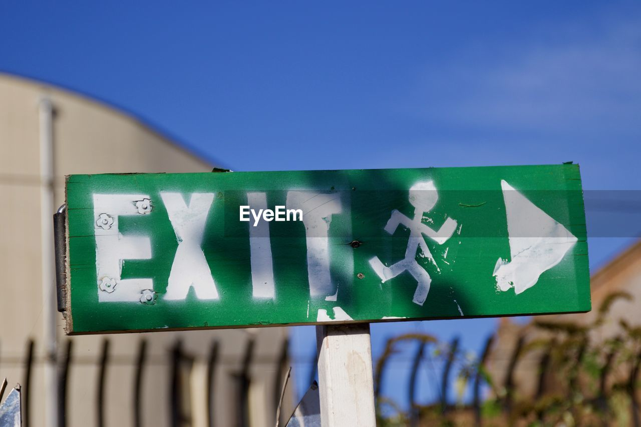 Close-Up Of Exit Sign Against Blue Sky