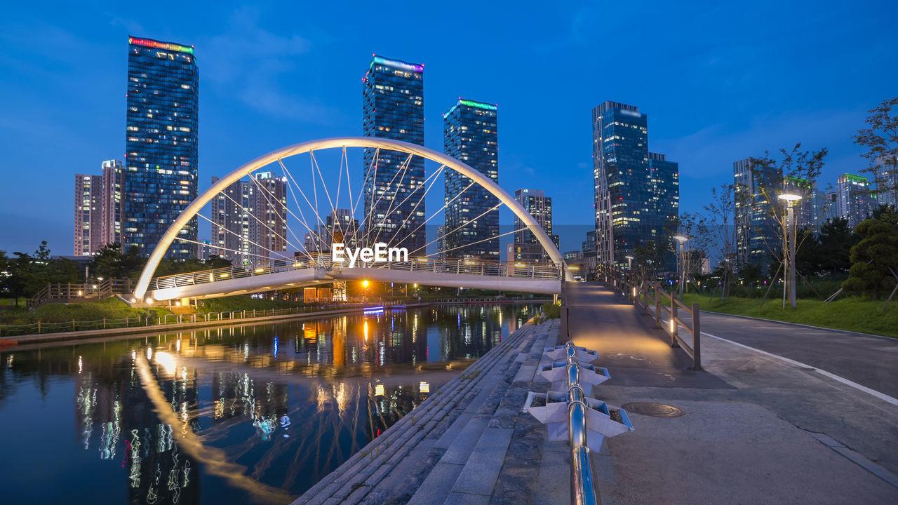 Illuminated Bridge And Buildings Against Sky At Night