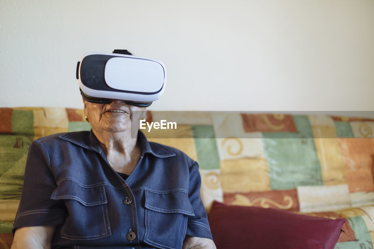one person, virtual reality simulator, men, real people, leisure activity, males, indoors, front view, technology, senior adult, lifestyles, adult, casual clothing, waist up, wireless technology, looking, mature adult, focus on foreground, connection, mature men, 3-d glasses