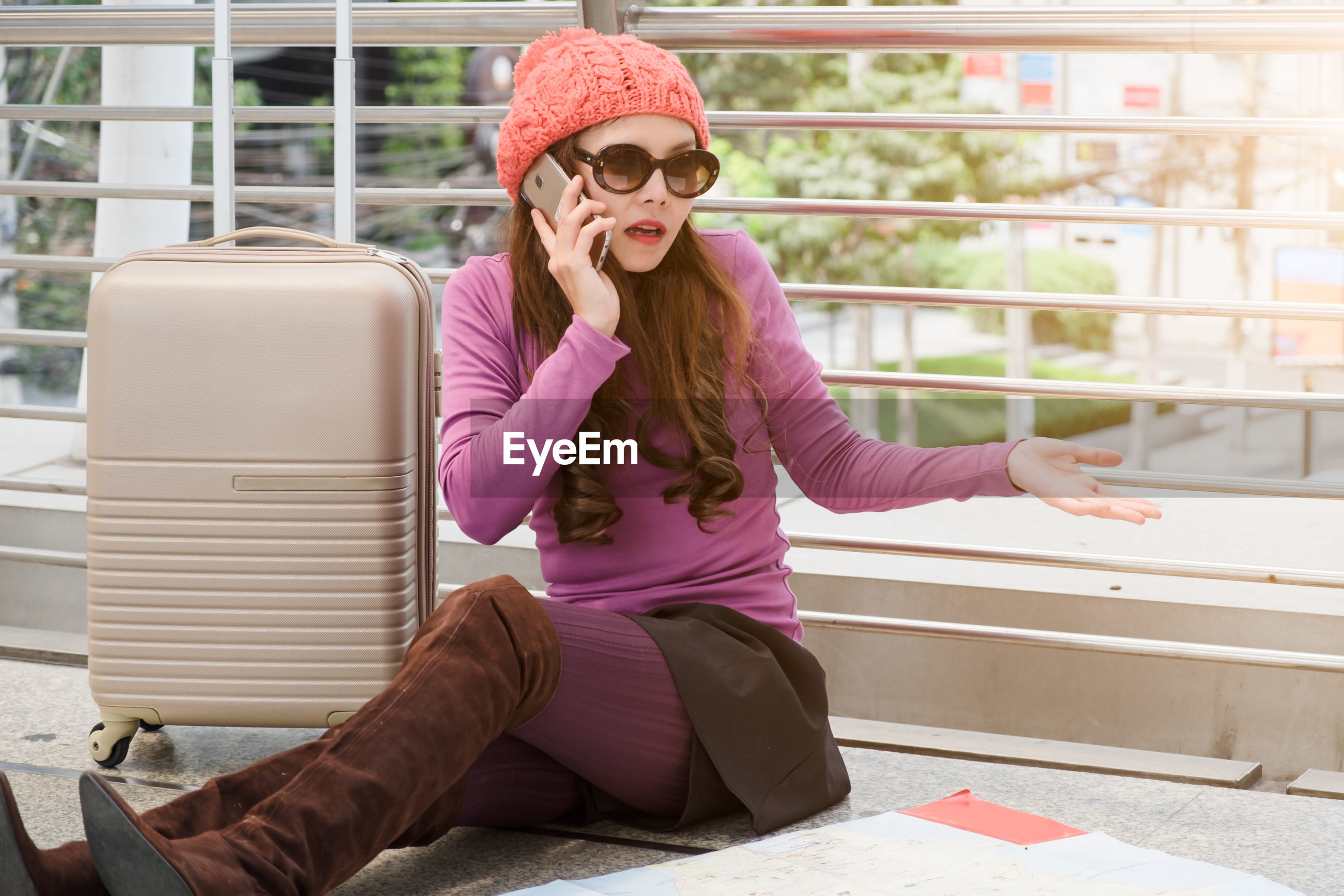 Woman talking on mobile phone while sitting with suitcase outdoors